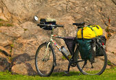 Loaded touring bicycle on rest break, next to a mauntain — Stock Photo