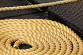 Close-up of an old frayed boat rope in circle, on the deck of a boat — 图库照片