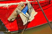 Closeup červené luk a rezavá kotva z rybářské lodi — Stock fotografie