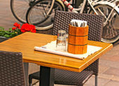 Patio with table and chairs, knifes and forks in a wooden stand — Stock Photo