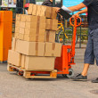 A fork pallet truck stacker with stack of boxes - Stok fotoğraf