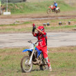 Stock Photo: Motocross racer greets spectators