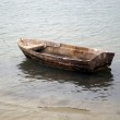Small wooden boat anchored on the beach — Stock Photo