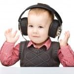 Cute little boy enjoying music using headphones — Stock Photo #10818654