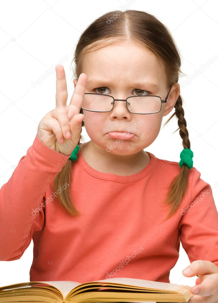 Cute little girl is showing Victory gesture with sad expression while reading book and wearing glasses, isolated over white — Stock Photo #10818856
