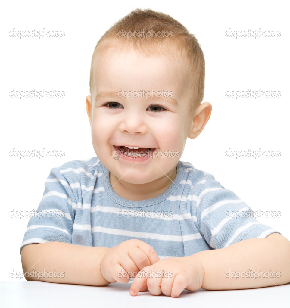 Portrait of a cute cheerful little boy, who is smiling while sitting at table, isolated over white — Stock Photo #10942356
