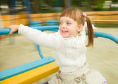 Cute little girl is riding merry-go-round — Stock Photo