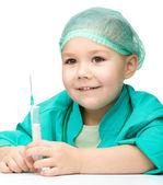 かわいい女の子は、注射器の医師を遊んでいます。 — ストック写真