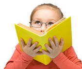 Little girl is dreaming while reading book — Foto Stock