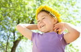 Portrait of a little girl with dandelion wreath — Stock Photo