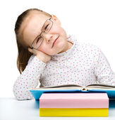 Cute little girl is tired of reading her book — Stock Photo