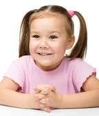 Happy little girl sits at a table and smile — Stock Photo