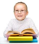 Cute cheerful little girl reading book — Stock Photo