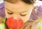 一个可爱的小女孩,嗅到花的肖像 — 图库照片