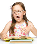 Cute little girl is yawning while reading book — Stock Photo