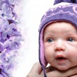 Portrait of newborn baby girl wearing violet winter hat — Stock Photo #11473597