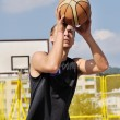 Basketball player shooting the ball - Stock Photo