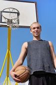 Basketball player posing in front of backboard — Stock Photo