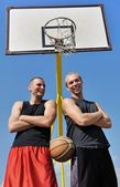 Two basketball players smiling on the court — Stock Photo