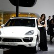 Stock Photo: Unidentified model with Porsche Hybrid sport car