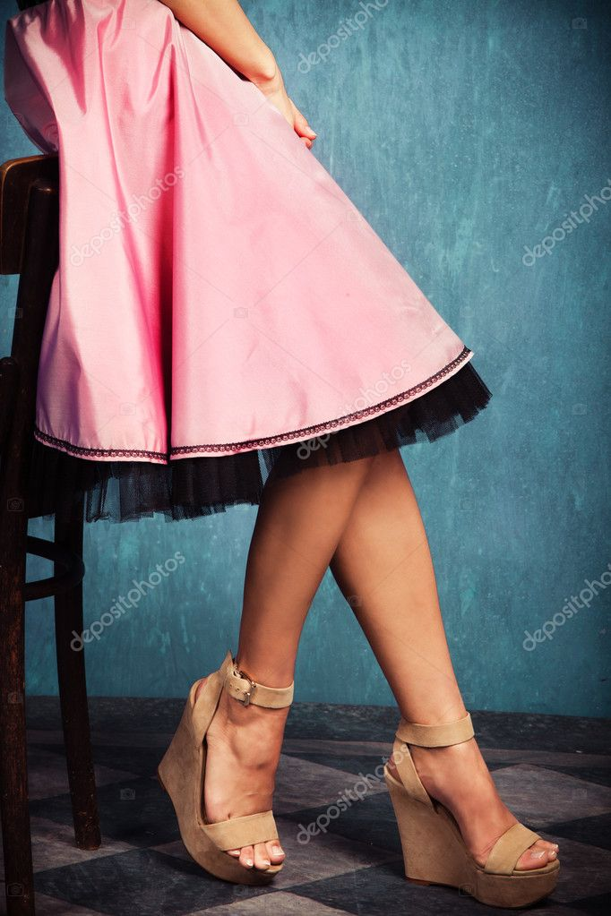 Female legs in wedge high heel shoes and romantic pink skirt — Stock Photo #10854330
