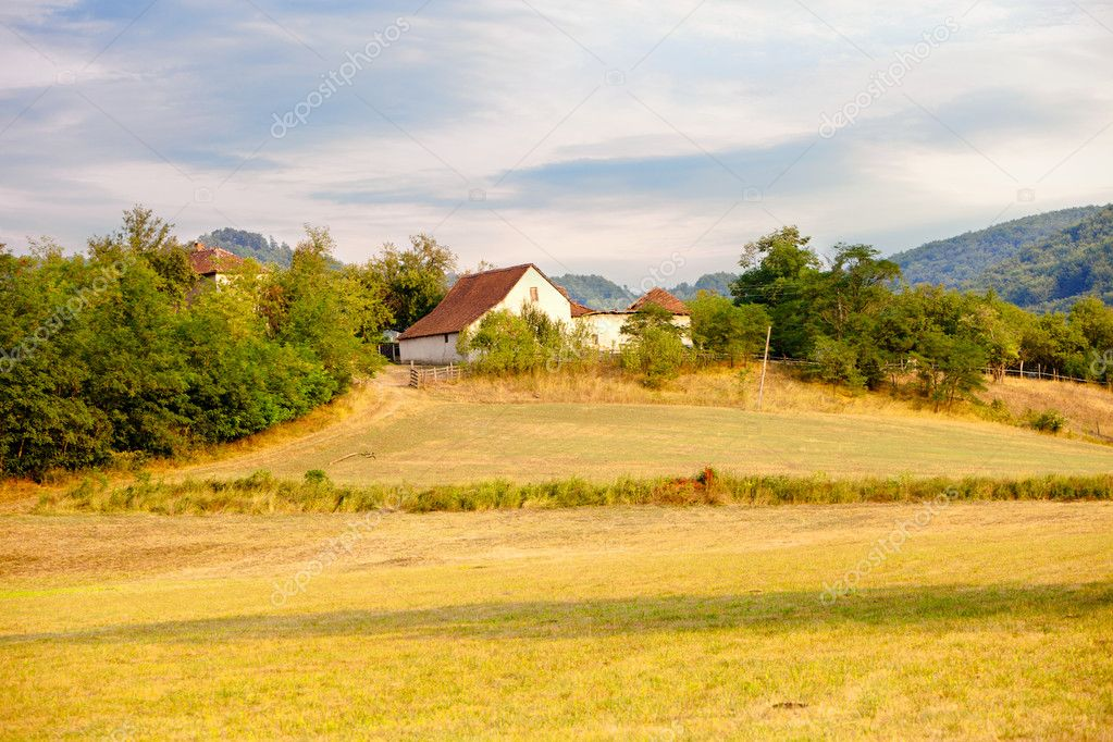 Farmhouse on glade hills and sky in background — Stock Photo #12359738