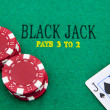 Stock Photo: Black jack with red poker chips in the background.
