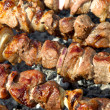 Stock Photo: Juicy slices of meat with sauce prepare on fire - kebab