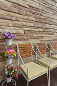 Colorful flowers chair and stone wall — Stock Photo