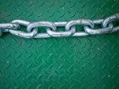 Cadena de plata en la placa de piso de acero verde — Foto de Stock