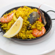 Portion of paella served in metal plate - Stock Photo
