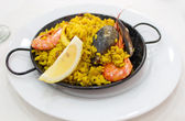 Portion of paella served in metal plate — Stock Photo