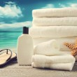Lotion, towels and sandals with ocean scene — Stock Photo