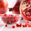Ripe pomegranates and glass bowl of seeds on white - Foto Stock