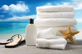 White towels and sandals with ocean scene — Stock Photo