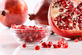 Ripe pomegranates and glass bowl of seeds on white — Stock Photo