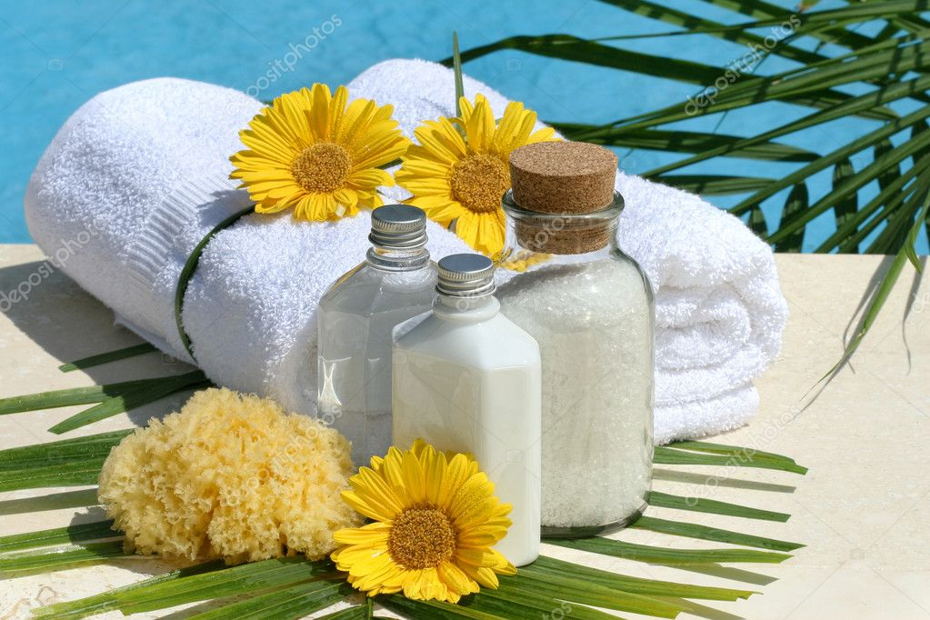 Spa products and white towels by the pool  Foto Stock #11116395
