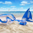 Goggles and toy sailboat in sand — Stock Photo