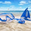 Goggles and toy sailboat in sand — Stockfoto