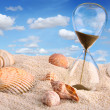 Hourglass in the sand with blue sky — Stok fotoğraf