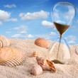 Hourglass in the sand with blue sky - Stockfoto