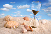 Hourglass in the sand with blue sky — Stock Photo