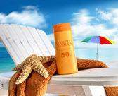Suntan lotion on chair at the beach — Stock Photo