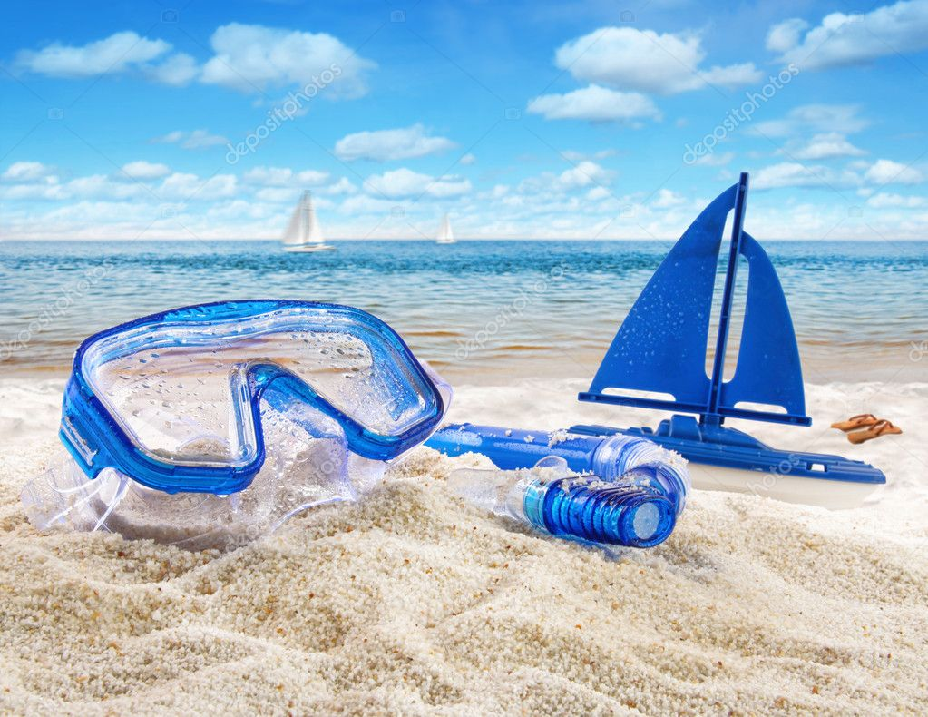 Goggles and toy sailboat in sand at the beach scene  Stock Photo #11642821