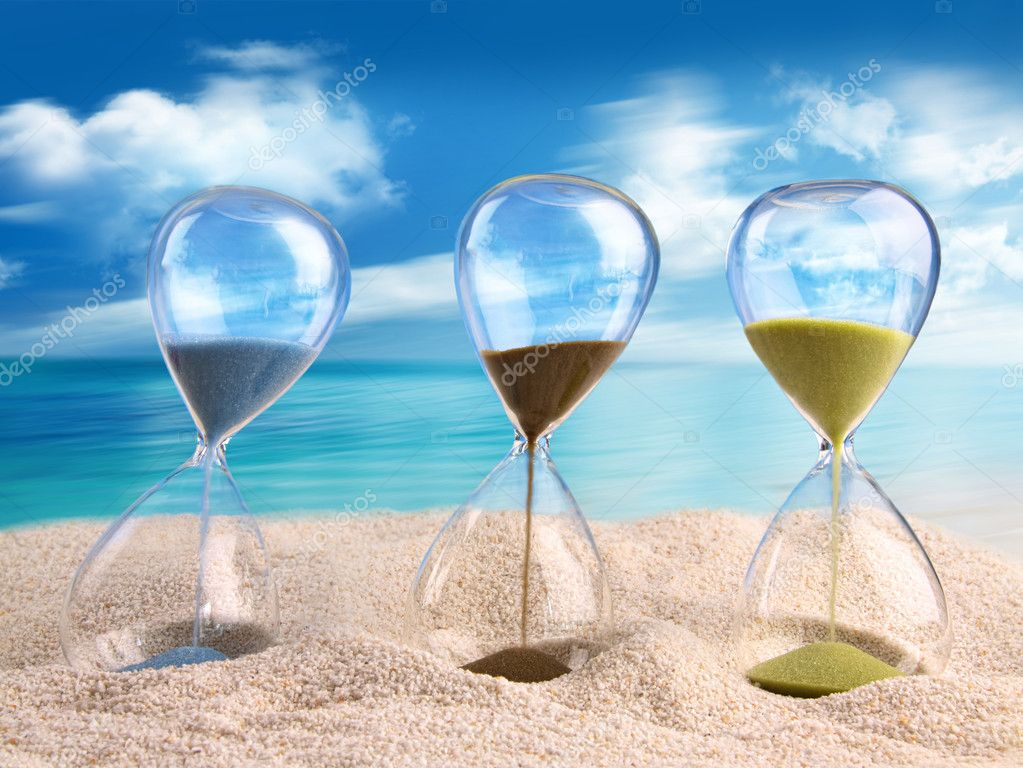 Three hourglass in the sand with blue sky  Stock Photo #11642915