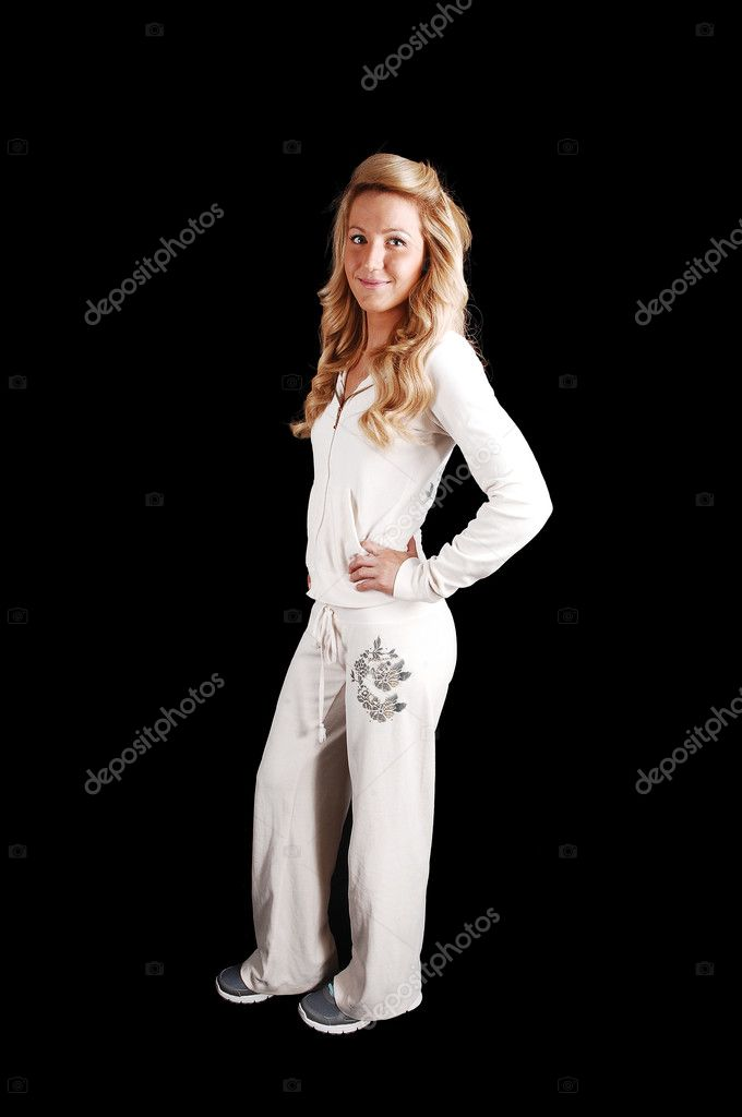 A beautiful young woman with long curly blond hair in a white track suitstanding in the studio for black background.  Stock Photo #10752063
