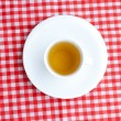 Cup of tea on plaid fabric — Stock Photo
