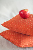 Apple lying on pillows on the bed — Стоковое фото