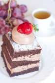 Beautiful cake with strawberry,grapes and tea on a white backgro — Stock Photo