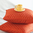 Cup lying on pillows on the bed — Stock Photo